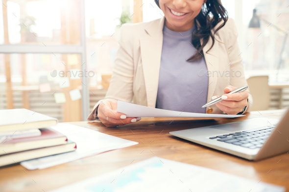 Smiling Businesswoman Reading Document at Workplace - Stock Photo - Images