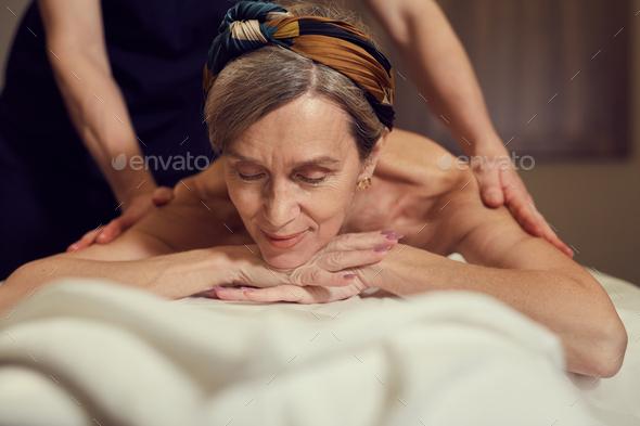 Smiling Senior Woman Enjoying Massage in SPA - Stock Photo - Images
