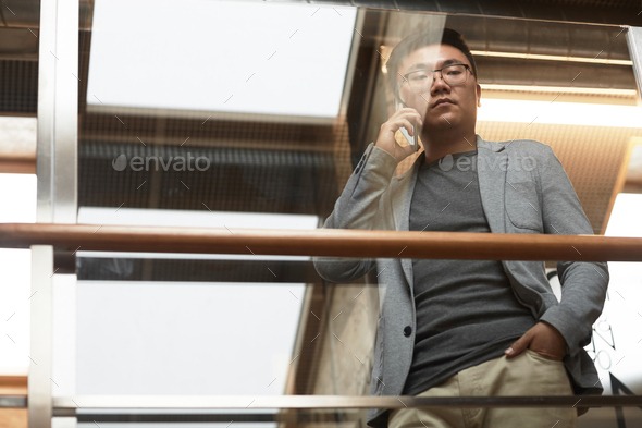Asian Businessman Speaking by Smartphone Low Angle - Stock Photo - Images