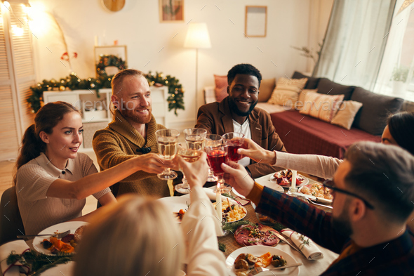 Group of Friends Raising Glasses at Dinner Party - Stock Photo - Images