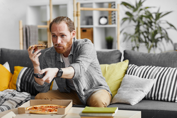Single Man Eating Pizza while Watching TV - Stock Photo - Images