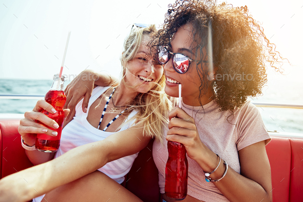 Girlfriends laughing over drinks while sitting on a boat - Stock Photo - Images