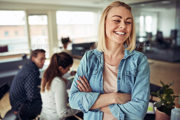 Laughing young businesswoman with colleagues at work in the background - Stock Photo - Images