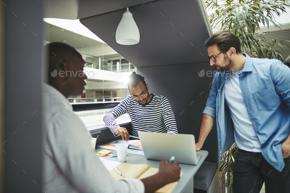 Diverse businessmen working in an office pod together - Stock Photo - Images