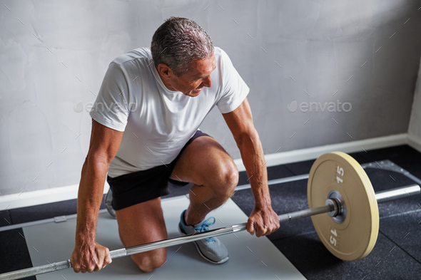 Mature man exercising with weights at the gym - Stock Photo - Images