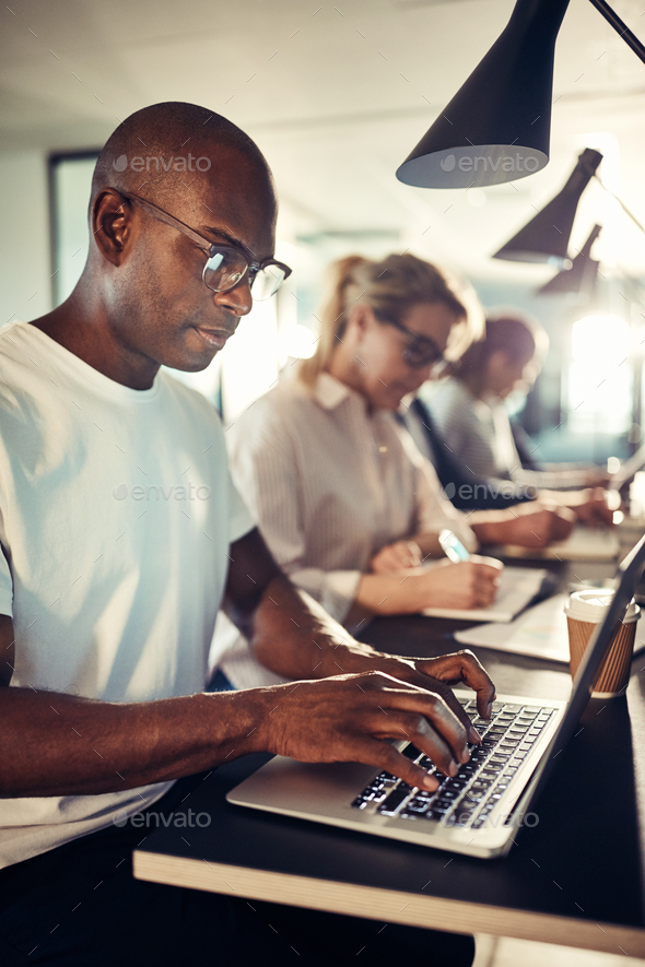 African designer working on his laptop in a busy office - Stock Photo - Images