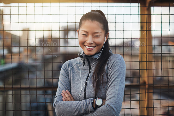 Sporty Asian woman standing with her arms crossed outdoors - Stock Photo - Images