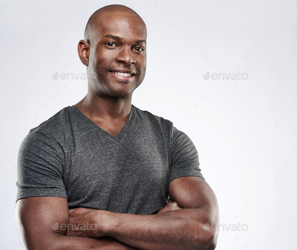 Man with folded muscular arms looking ahead - Stock Photo - Images