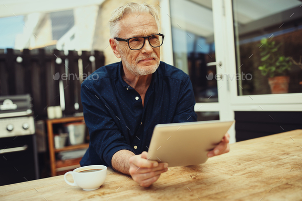 Content senior man holding a tablet and drinking coffee outside - Stock Photo - Images
