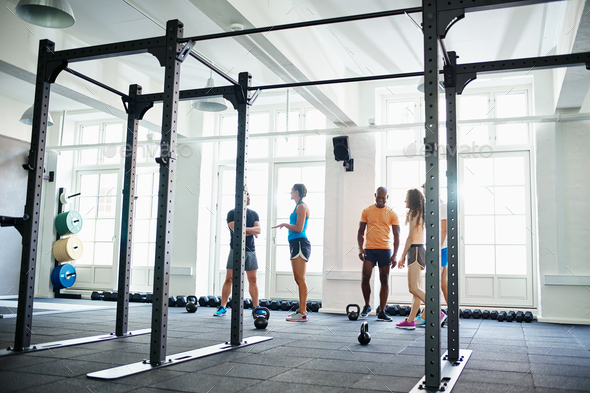 Smiling people in sportswear talking together in a gym - Stock Photo - Images