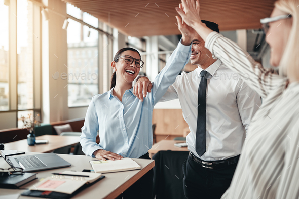 Laughing businesspeople high fiving together in an office - Stock Photo - Images