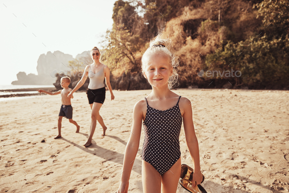 Smiling little girl walking along a beach with her family - Stock Photo - Images