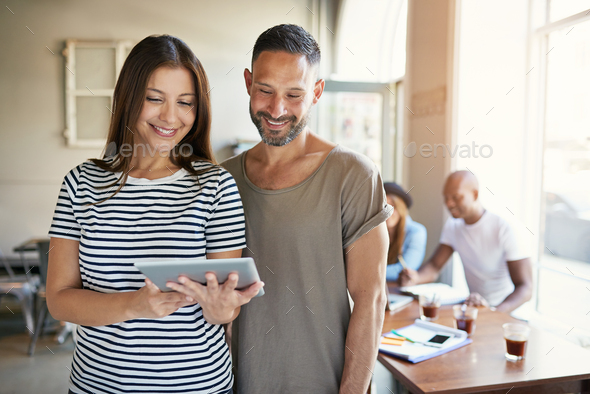 Female showing touch pad to male co-worker - Stock Photo - Images