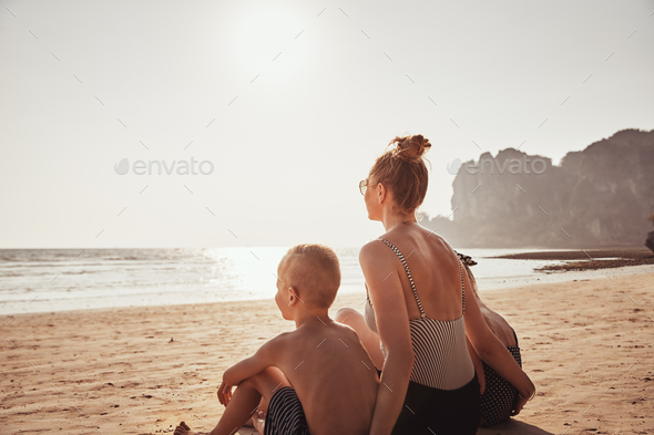 Mother and children enjoying the view from a sandy beach - Stock Photo - Images