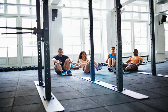Focused group of people doing crunches together in a gym - Stock Photo - Images
