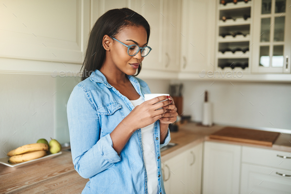 Young African woman drinking a cup of coffee at home - Stock Photo - Images