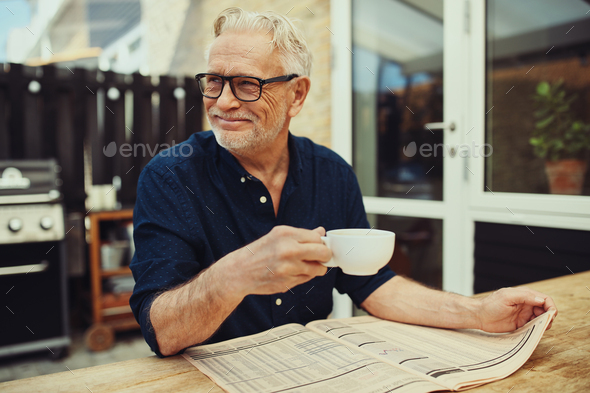 Smiling senior man drinking coffee and reading a newspaper outside - Stock Photo - Images