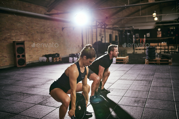 Sportsmen doing exercise with disks from squat - Stock Photo - Images