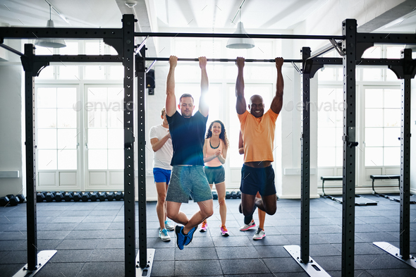 People watching two men doing chin ups in a health club - Stock Photo - Images