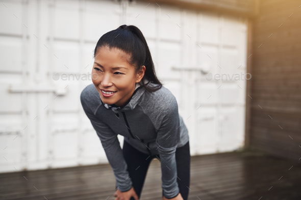 Smiling young Asian woman taking a break from her run - Stock Photo - Images
