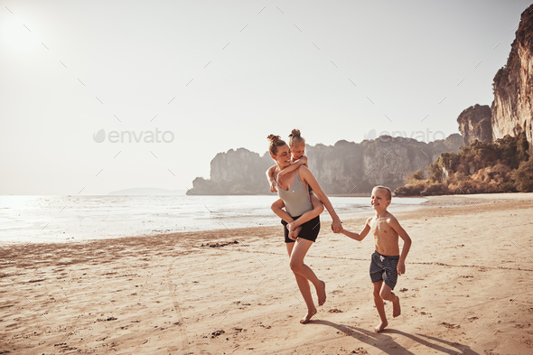 Laughing family playfully running on a beach in summer - Stock Photo - Images
