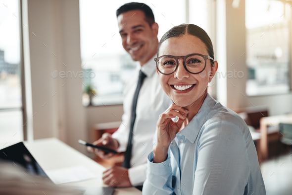Businesswoman smiling while working with a colleague in an office - Stock Photo - Images