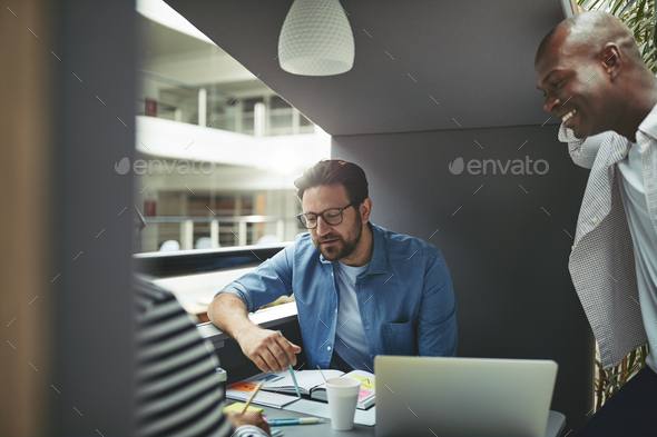 Diverse team of businessmen working in an office meeting pod - Stock Photo - Images