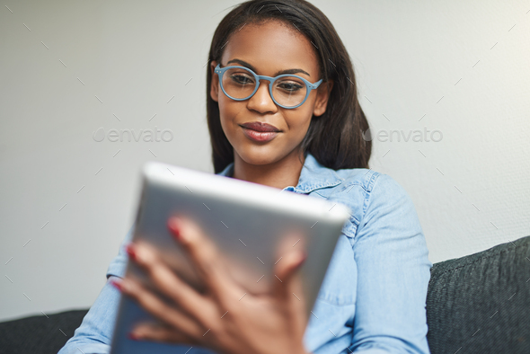 Smiling African woman using a digital tablet on her sofa - Stock Photo - Images