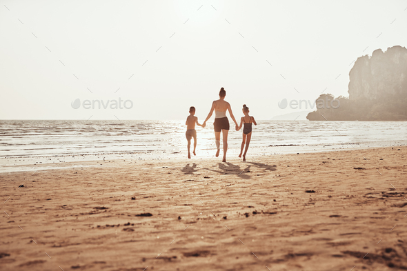 Mother and children holding hands and skipping along a beach - Stock Photo - Images