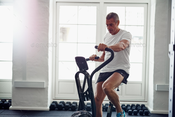 Mature man riding a health club stationary bike - Stock Photo - Images