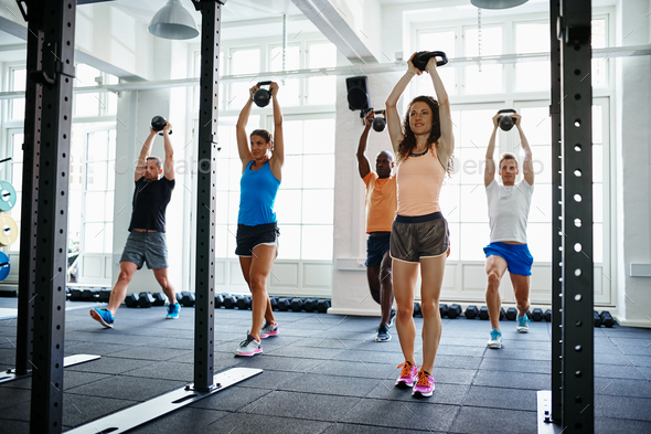 Fit people working out with weights in a gym - Stock Photo - Images