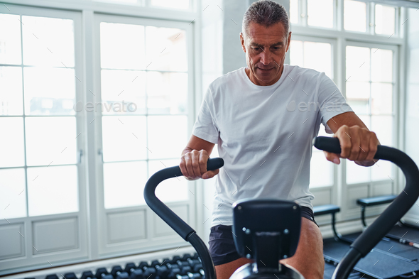 Mature man exercing on a stationary bike at the gym - Stock Photo - Images