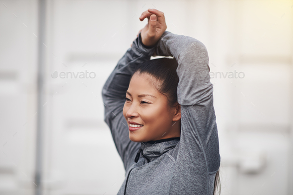 Smiling young Asian woman stretching before going for a run - Stock Photo - Images