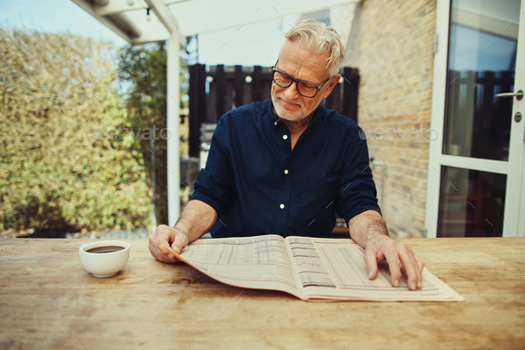 Senior man relaxing outside with a coffee and newspaper - Stock Photo - Images