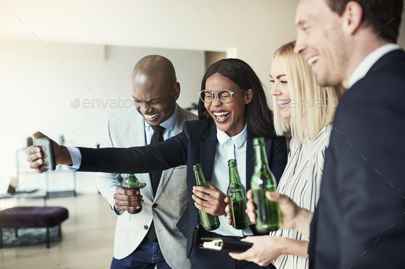 Laughing businesswoman taking selfies over drinks with colleagues after work - Stock Photo - Images