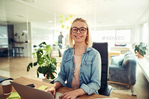 Smiling businesswoman sitting at her desk in an office desk - Stock Photo - Images
