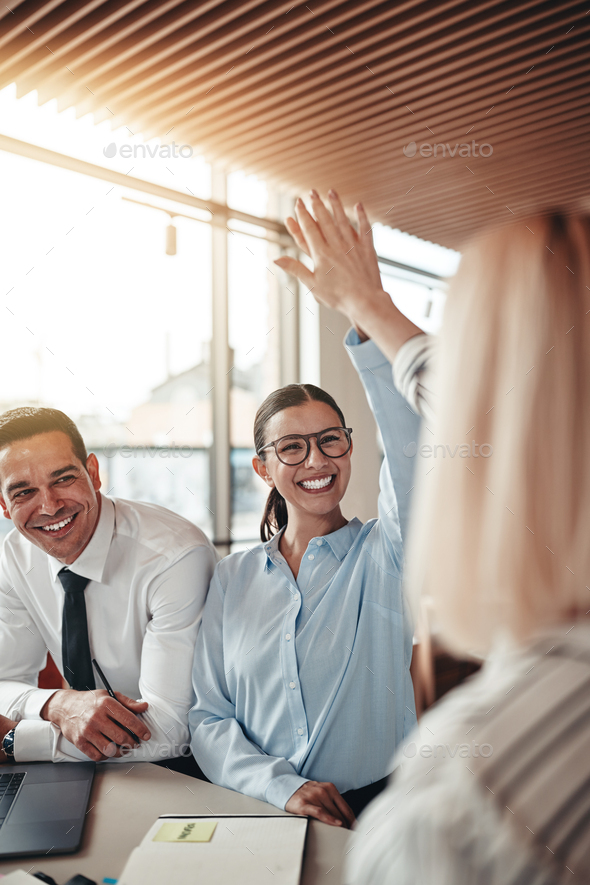 Laughing businesswomen high fiving together in an office - Stock Photo - Images