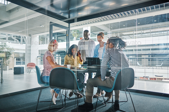 Diverse businesspeople working around a table in an office boardroom - Stock Photo - Images