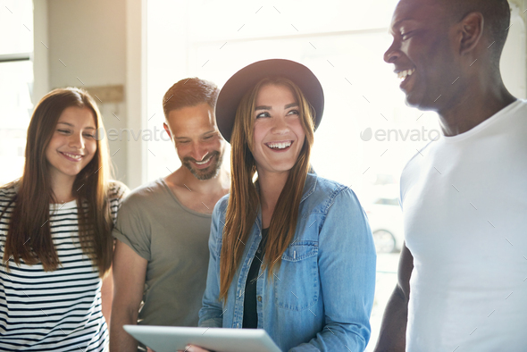 Four diverse happy adults looking at tablet - Stock Photo - Images