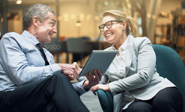 Smiling businesswoman shaking hands with a colleague in an office - Stock Photo - Images