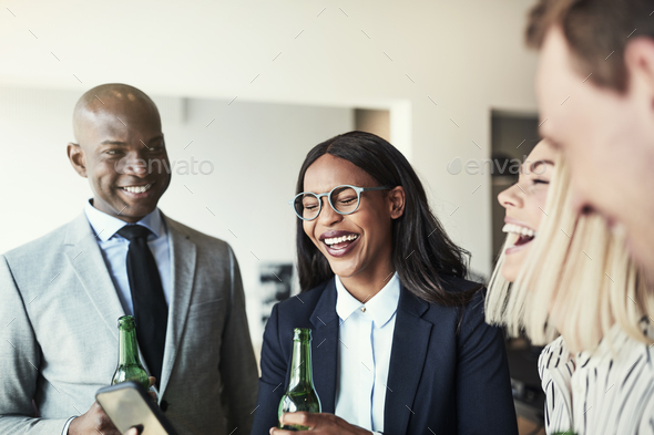 Diverse group of laughing businesspeople having drinks in an office - Stock Photo - Images