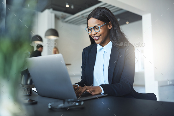 Smiling African American businesswoman using a laptop at her desk - Stock Photo - Images