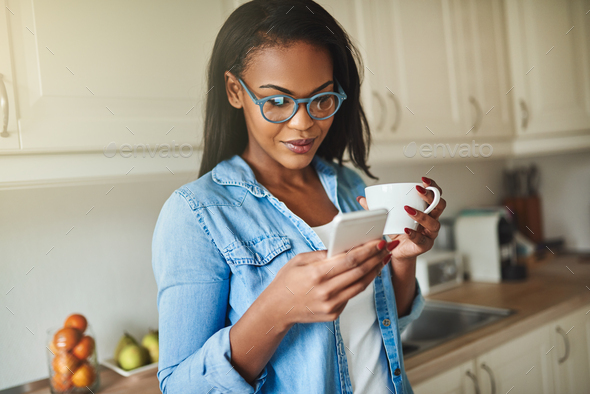 Young African woman drinking coffee and reading text messages - Stock Photo - Images