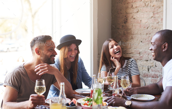 Young friends having dinner and laughing together - Stock Photo - Images