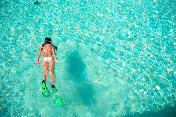 Young woman snorkeling in tropical water on vacation - Stock Photo - Images