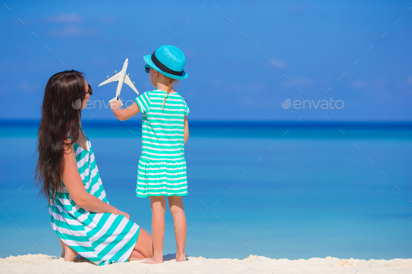 Young woman and little girl with miniature of airplane at beach - Stock Photo - Images