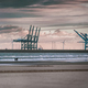 Couple walking on a beach with port crane in the background - PhotoDune Item for Sale