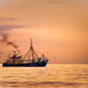 Fisherman boat on the sea with birds behind during sunset - PhotoDune Item for Sale