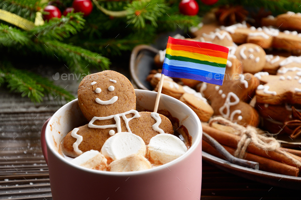 Pink mug with hot chocolate marshmallows and gingerbread man with rainbow flag - Stock Photo - Images