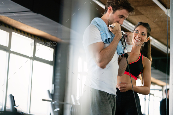 Young fit man doing exercises with personal trainer in gym - Stock Photo - Images